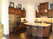 Beautiful model home in central Texas with kitchen cabinets by Burrows Cabinets in knotty alder and cabinet doors by TaylorCraft Cabinet Door Company