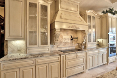 kitchen with wood vent hood and glass panel cabinet doors in paint grade maple
