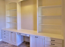 white built in bookshelves with desk